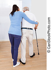 Caregiver Assisting Senior Man To Walk With Stick