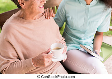 Caregiver caring about female pensioner in the garden