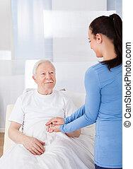 Caregiver Consoling Senior Man