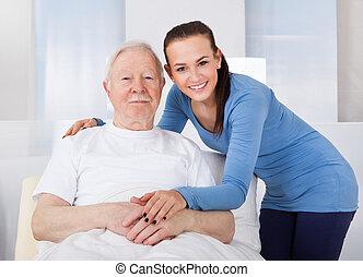 Caregiver Consoling Senior Man - Young female caregiver...