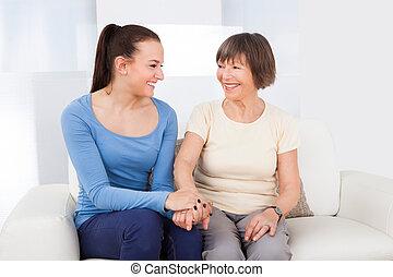 Caregiver Consoling Senior Woman - Young female caregiver...