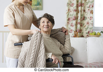 Caregiver covering senior woman with a blanket