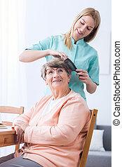 Caregiver doing senior woman's hair