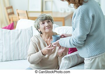 Caregiver giving elder woman coffee