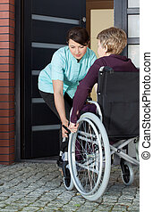Caregiver helping disabled woman entering home - Female...