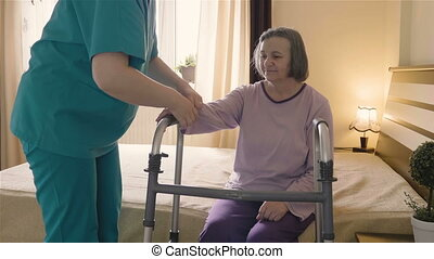 Caregiver helping senior woman getting up and walk with a walker