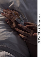 Caregiver holding elderly patient's hand - Close-up of...