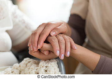 Caregiver holding senior woman's hands - Close-up photo of a...