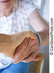 Caregiver holding seniors hand on porch