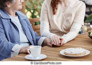 Caregiver holds the hand of elderly woman while sitting at a...
