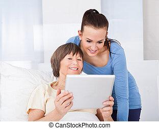 caregiver, i, starsza kobieta, używając, palcowa pastylka