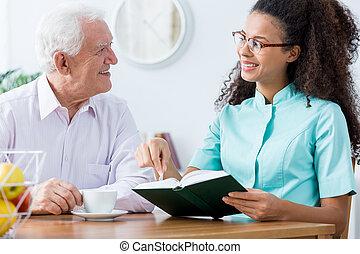 African American caregiver keeping senior man company