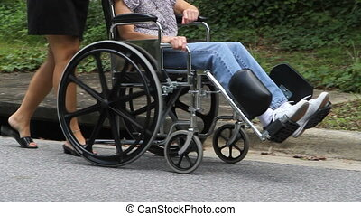 Lower body view of woman caregiver as she pushes disabled senior citizen in a wheelchair down the street.