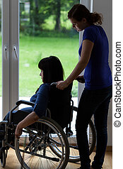Caregiver pushing wheelchair with disabled woman