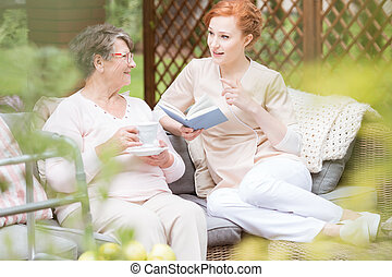 Caregiver reading book while senior woman drinking tea on the terrace