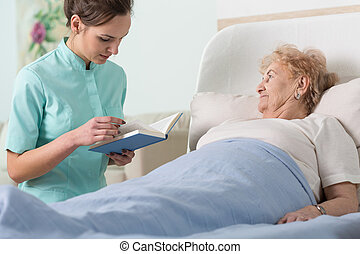 Caregiver reading ill patient book - Close-up of caregiver ...