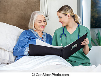 Caregiver Showing Medical Reports To Senior Woman - Smiling...