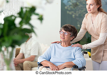 Caregiver taking care of disabled elderly woman on the wheelchair