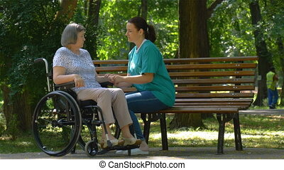 Caregiver talking to disabled senior woman in wheelchair outdoors