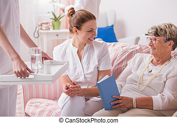 Caregiver with medicines for elderly patient