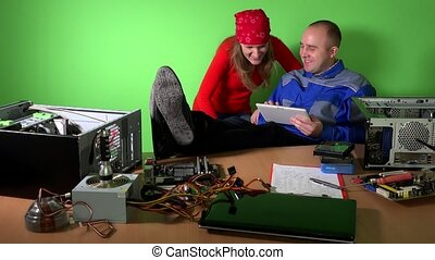 Careless technician man and woman have fun with tablet...