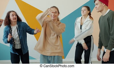 Careless young people are enjoying dance practice in hip-hop dancing center, teens are wearing trendy clothing and headwear. Youth lifestyle and hobby concept.