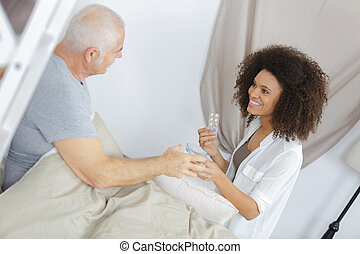 Carer administering medication to patient