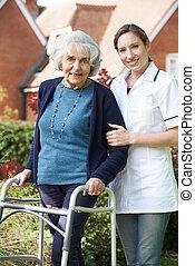 carer, ajudando, mulher sênior, andar, em, jardim, usando, andando armação