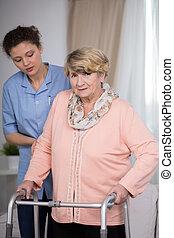 Carer and older woman - Female carer helping older woman...