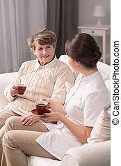 Carer assisting elderly woman