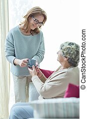 Carer helping elder woman - Female carer helping elder woman...