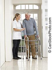 Carer Helping Elderly Senior Man Using Walking Frame