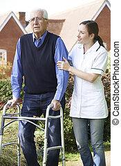 Carer Helping Senior Man To Walk In Garden Using Walking Frame