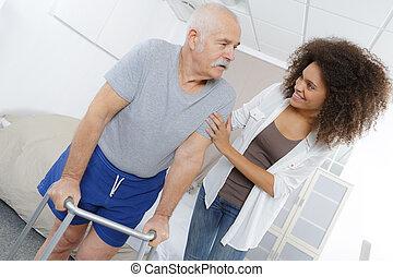 carer helping senior man walk with frame