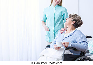 Carer helping senior woman in rest home