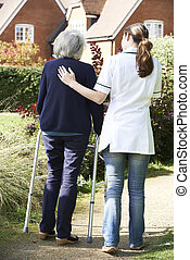 Carer Helping Senior Woman To Walk In Garden Using Walking Frame