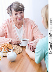Carer keeping company senior woman - Young female carer...