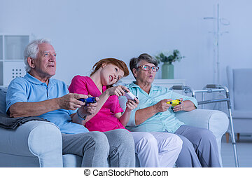 Carer playing video games with elderly couple
