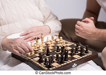 Photo of carer playing chess with rest home resident