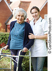 carer, portion, femme aînée, marcher, dans, jardin, utilisation, cadre promenade