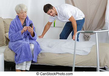 carer preparing bed for an elderly woman