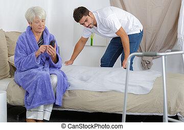 carer, przygotowując, łóżko, dla, na, starsza kobieta