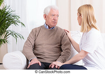 Carer supporting senior man - Young female carer supporting...