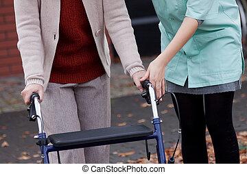 Carer teaching using walker - Carer teaching elder lady...