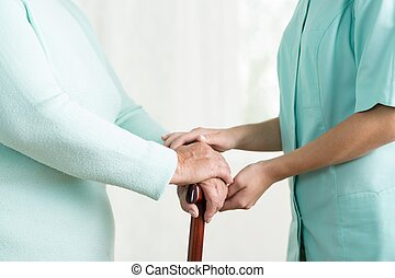 Carergiver holding hand of female