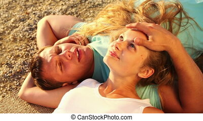 Caress - Affectionate couple lying on the ground talking and...