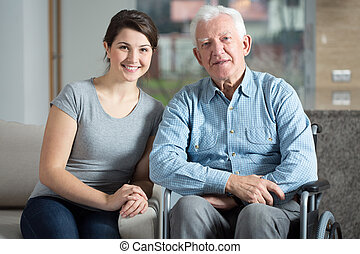 Young pretty female caretaker and elderly man on a wheelchair