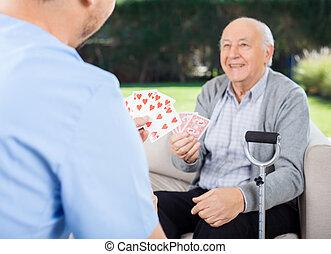 Caretaker And Senior Man Playing Cards At Nursing Home