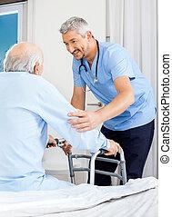 Male caretaker assisting senior man to use walking frame in bedroom at nursing home