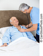 Caretaker Checking Senior Man With Stethoscope